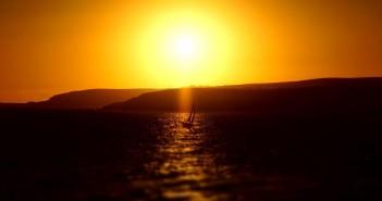 Żaglówka na tle zachodzącego słońca. (fot. Michał Banach)
