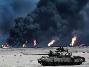 Zniszczony iracki czołg T-55 na tle palących się szybów naftowych