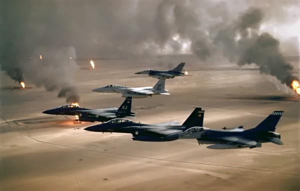 Formacja samolotów F-15 i F-16 nad płonącymi szybami naftowymi