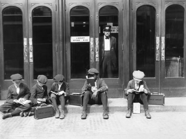 Dzieciaki siedzące przed wejściem do biblioteki