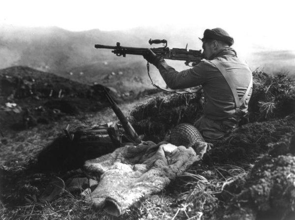 Kanadyjski żołnierz oglądający porzucony japoński karabin maszynowy