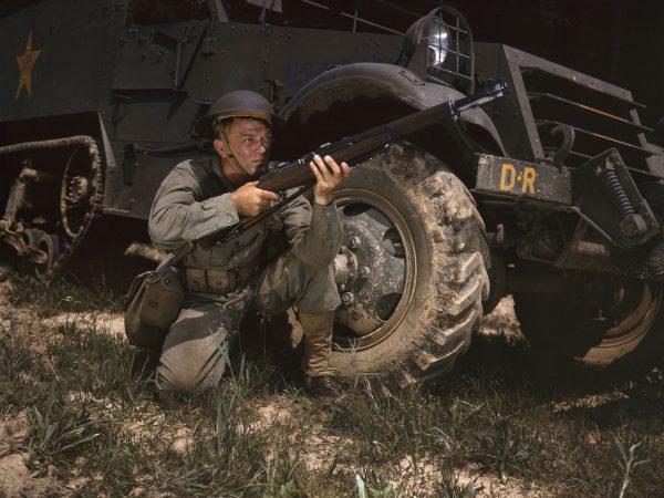 Amerykański żołnierz z karabinem M1 Garand obok transportera półgąsienicowego M3 Half-Track podczas manewrów w Fort Knox - 1942 rok (fot. Alfred Palmer)